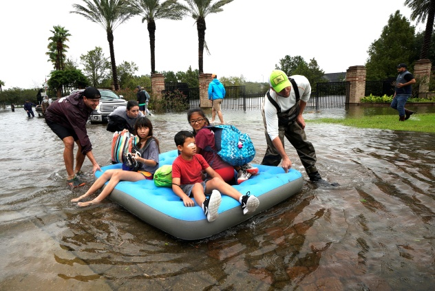 A family is evacuated on an air mattress from the Hurricane Harvey floodwaters in Houston